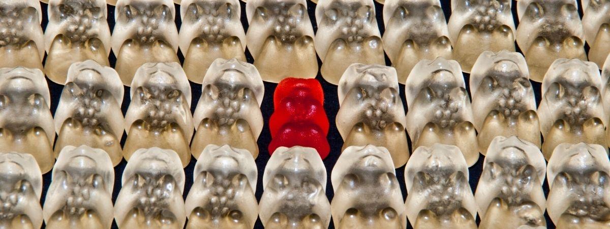 rotes Gummibärchen zwischen lauter weißen