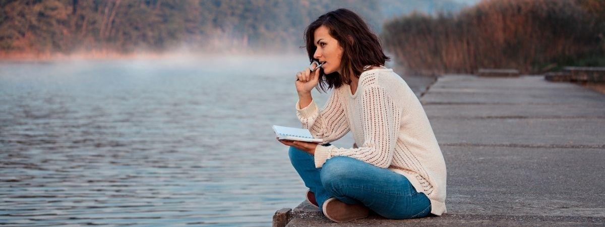 Frau mit Schreibblock am See