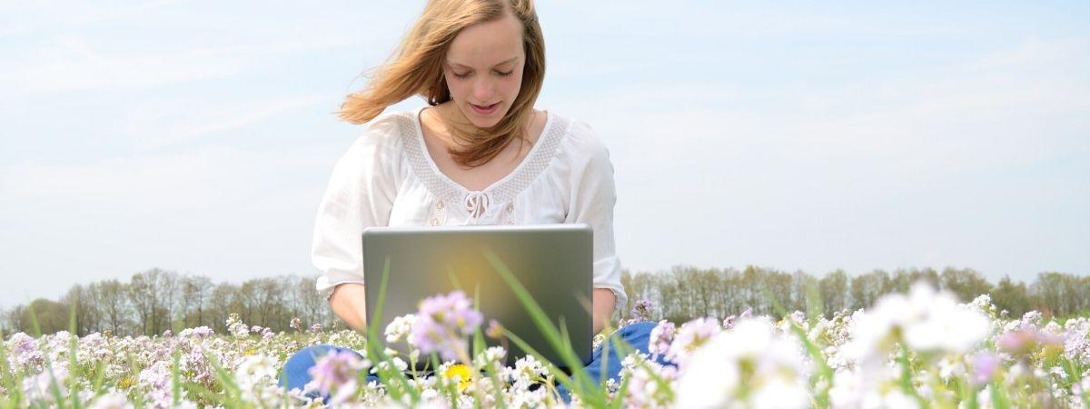 Frau mit Laptop auf Blumenwiese